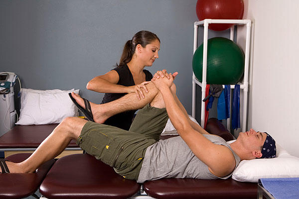 Physical therapist assists with stretches.