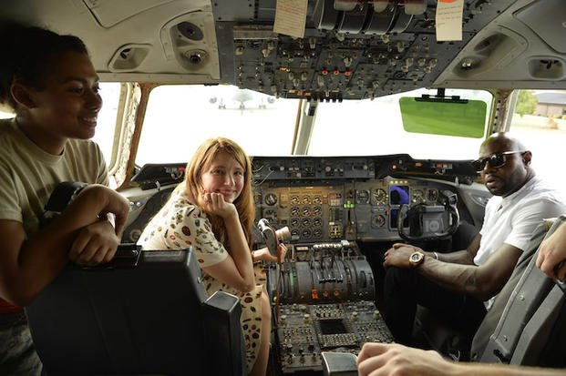 The Magnificent 7 director Antoine Fuqua (right) and movie actress Haley Bennett visit the cockpit of a USAF KC-10 tanker prior to a USO-sponsored film premiere at Joint Base McGuire-Dix-Lakehurst, New Jersey, September 18, 2016. The cast members and director toured the flightline, greeted service members and met with military families to extend their appreciation for their service. USO Photo by Mike Theiler
