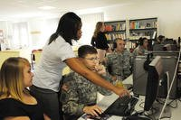Theresita Cliett, Army Career and Alumni Program career counselor, talks a soldier and his wife through the USAJobs.gov job website. (Chelsea Bissell/U.S. Army)
