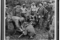 A casualty from the fighting at Guadalcanal is transferred from a makeshift stretcher before being taken through jungle and down river to a field hospital. (Photo courtesy Library of Congress)