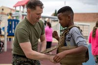 A U.S. Marine assigned to Special Purpose Marine Air-Ground Task Force-Crisis Response Africa helps a child into a protective vest during a gear demonstration. (U.S. Marine Corps/Taylor W. Cooper)