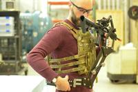 Army Research Lab engineer Dan Baechle demonstrates how to strap on a mechanical arm designed to reduce soldier fatigue and improve weapon's accuracy. (Photo: U.S. Army)