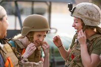 Brandi Pompa and Katherine Shelton adjust their kevlar helmets during their unit's Jane Wayne Spouse Appreciation Day aboard the Marine Corps Air Ground Combat Center, Twentynine Palms, Calif., April 3, 2018. (U.S. Marine Corps/Rachel K. Porter)