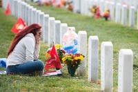 A woman visits her brother's grave in Arlington National Cemetery's Section 60. (U.S. Army/Rachel Larue)