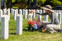 Alison Malachowski tends to the grave of her son, U.S. Marine Corps Staff Sgt. James Malachowski, in Section 60 of Arlington National Cemetery, July 22, 2015. Staff Sgt. Malachowski was killed by an improvised explosive device during his fourth combat deployment on March 20, 2011, while his unit was raising the Afghanistan national flag over a small compound near Patrol Base Dakota in Marjah Province. (U.S. Army/Ken Scar)
