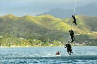 U.S. Navy divers with the U.S. Navy SEAL Delivery Vehicle Team 1, Naval Special Warfare Group 3, dangle from a rope attached to an Army UH-60 Black Hawk helicopter during SPIE training at Marine Corps Air Station Kaneohe Bay, Hawaii, June 18, 2013. (U.S. Army/Capt. Richard Barker)