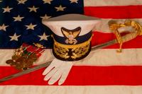Officer's combination cover, sword, white gloves and medal rack laying upon an American flag. (U.S. Coast Guard photo)