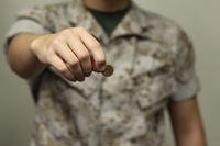 Servicemember holding a penny.