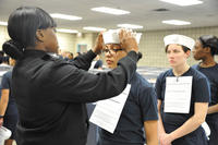 "Engineman 2nd Class Shanice Floyd, a recruit division commander, ensures the proper fit of Seaman Recruit Megan Marte's white enlisted hat, or ""Dixie cup,"" during uniform issue at Recruit Training Command. Sue Krawczyk/Navy"