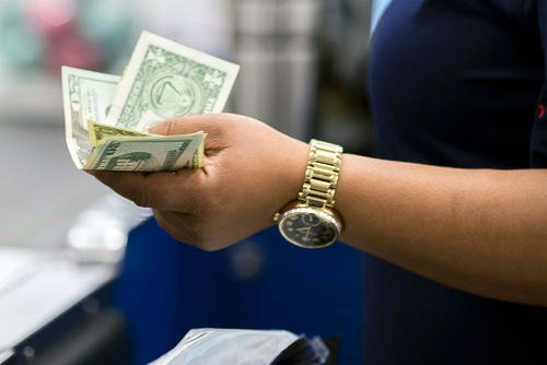 A woman holds money (U.S. Army/Nell King)
