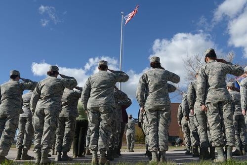 Airmen salute the American flag as it is lowered during the women's retreat ceremony at Ellsworth Air Force Base, S.D., April 7, 2016. (U.S. Air Force/Airman Donald C. Knechtel/Released)